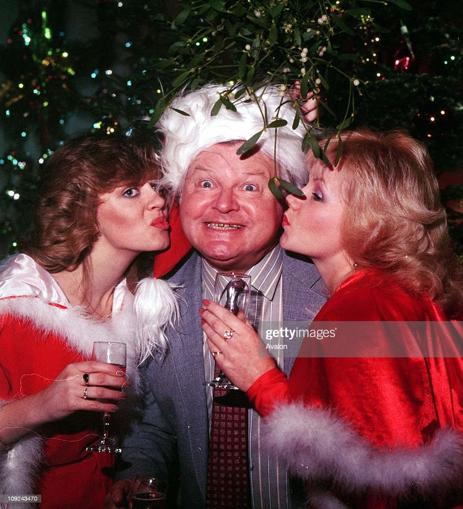 Writer benny hill being kissed under the mistletoe by two of his hill