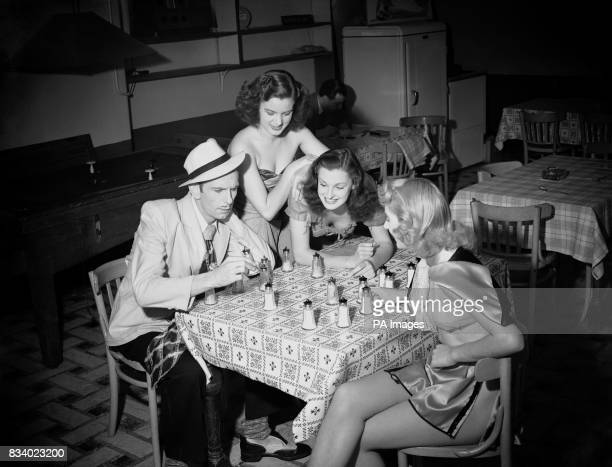 British comedian Arthur English plays pepper pot draughts with Windmill girl Madeleine Hearne watched by Irene King and Beryl Catlin in the canteen...