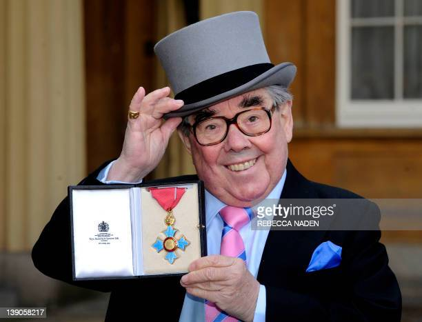 British comedian Ronnie Corbett poses with his medal after he received the honour Commander of the Order of the British Empire from Britain's Queen...