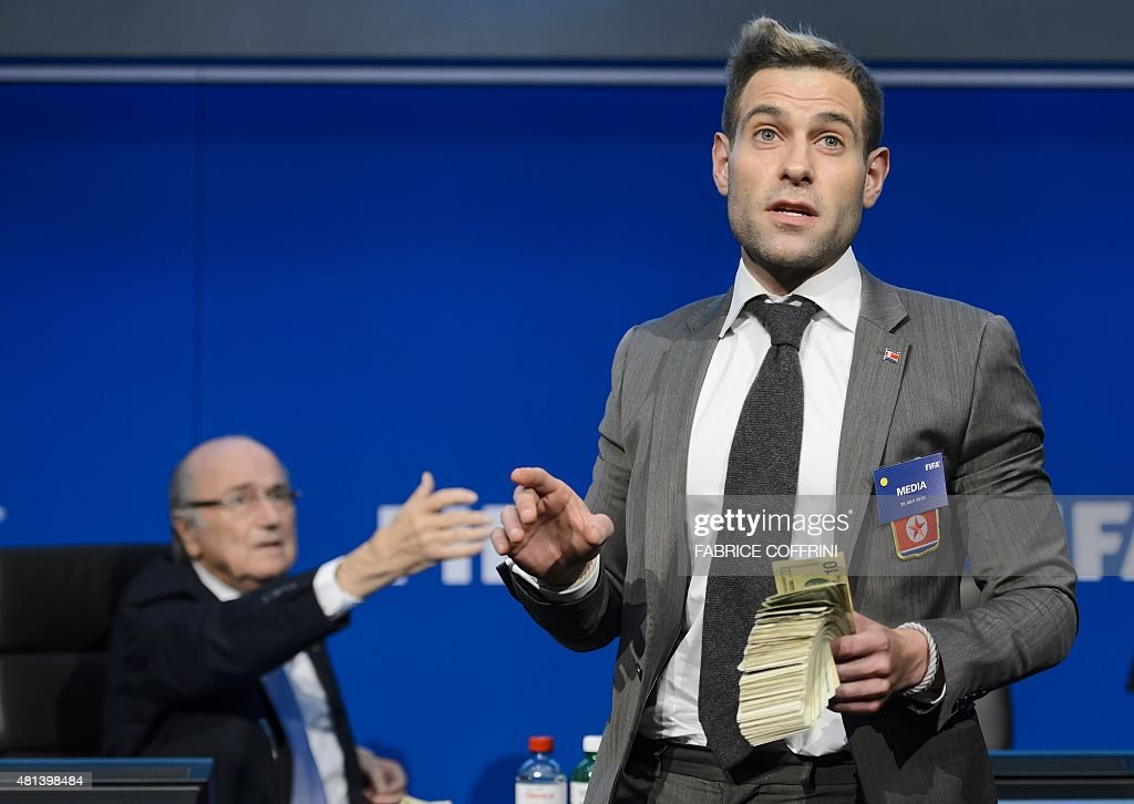 British comedian Simon Brodkin (R) holds fake dollars note next to FIFA president Sepp Blatter gestures during a protest at a press conference at the football's world body headquarter's on July 20, 2015 in Zurich. A British comedian on interrupted a press conference by Sepp Blatter in Zurich throwing paper money in front of the bemused FIFA president just as he was about to speak.