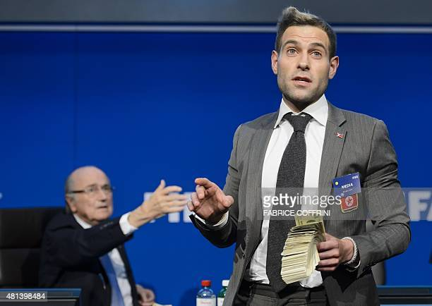 British comedian Simon Brodkin holds fake dollars note next to FIFA president Sepp Blatter gestures during a protest at a press conference at the...