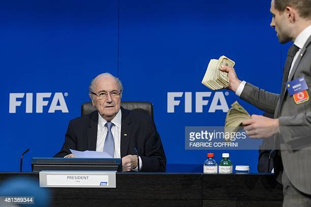 British comedian Simon Brodkin holds fake dollars notes in front of FIFA president Sepp Blatter during a press conference at the football's world...