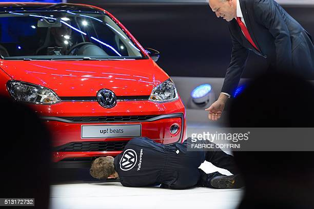 British comedian Simon Brodkin inspects a new model at German carmaker Volkwagen stand next to Volkwagen board member Juergen Stackmann as he...