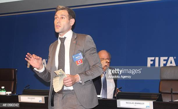 British comedian Simon Brodkin throws money at FIFA President to protest while Sepp Blatter is making a press conference following a meeting about...