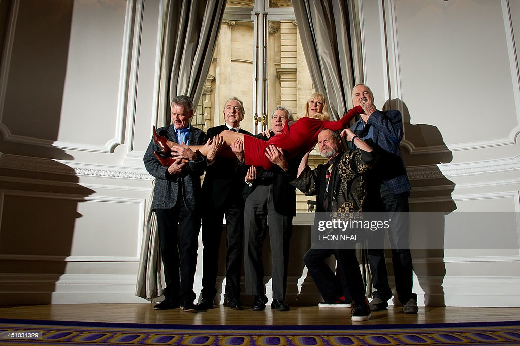 British comedy troupe Monty Python, (L-R) Michael Palin, Eric Idle, Terry Jones, Terry Gilliam and John Cleese hold up Python colaborator Carol Cleveland as they pose for a photograph during a media event in central London on November 21, 2013. Cue endless jokes about resting parrots -- the five surviving members of Monty Python, Britain's cult comedy troupe, announced on November 21 they will take to the stage again next year, three decades after their last performance together. AFP PHOTO / LEON NEAL