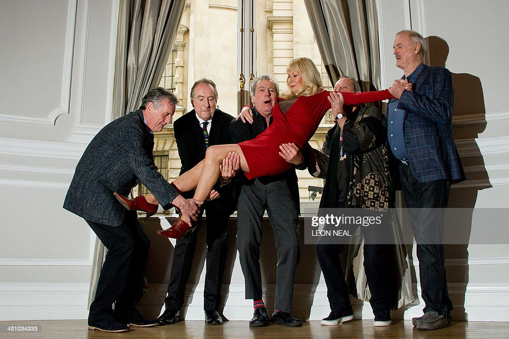 British comedy troupe Monty Python, (L-R) Michael Palin, Eric Idle, Terry Jones, Terry Gilliam and John Cleese hold up Python colaborator Carol Cleveland as they pose for a photograph during a media event in central London on November 21, 2013. Cue endless jokes about resting parrots -- the five surviving members of Monty Python, Britain's cult comedy troupe, announced on November 21 they will take to the stage again next year, three decades after their last performance together.