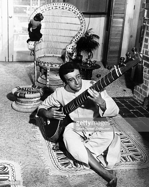 British comic actor Peter Sellers playing the sitar as Hrundi V Bakshi in 'The Party' directed by Blake Edwards 1968