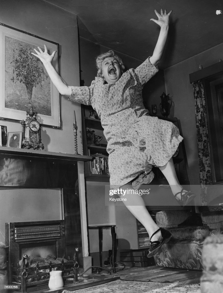British comic actress and music hall singer and comedienne Tessie O'Shea (1917 - 1995) leaping for joy at home. Original Publication: People Disc - HH0381