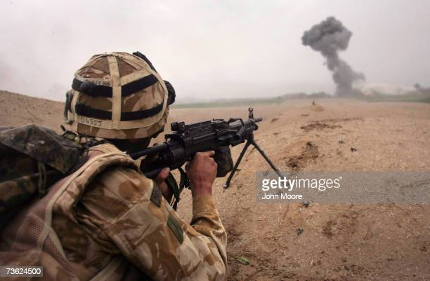British commando Lee Oliver fires at Taliban only 400 meters away as a plume of smoke rises from an airstrike during a sunrise attack on Taliban...