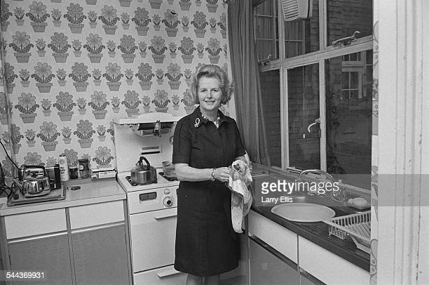 British Conservative Party Education Secretary and MP for Finchley Margaret Thatcher poses washing dishes in a kitchen during the UK general election...