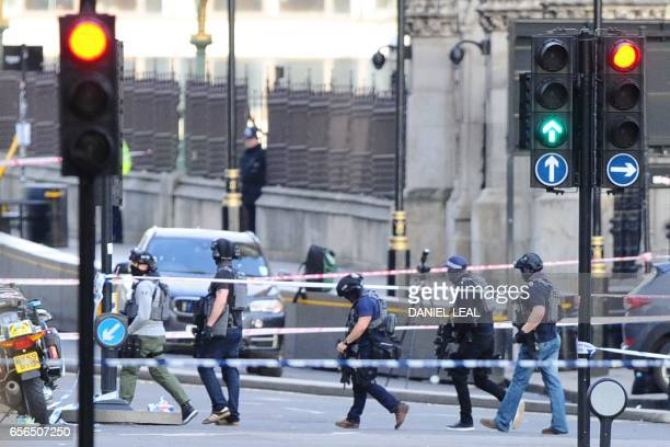 British counterterrorism police officers carry their weapons as they work on Westminster Bridge adjacent to the Houses of Parliament in central...