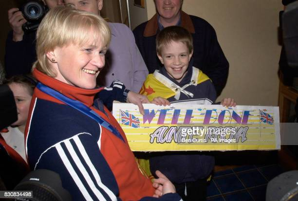 British curling skip Rhona Martin wearing her gold medal is greeted on her return to Glasgow by a nephew carrying a banner reading 'Well Done Auntie...