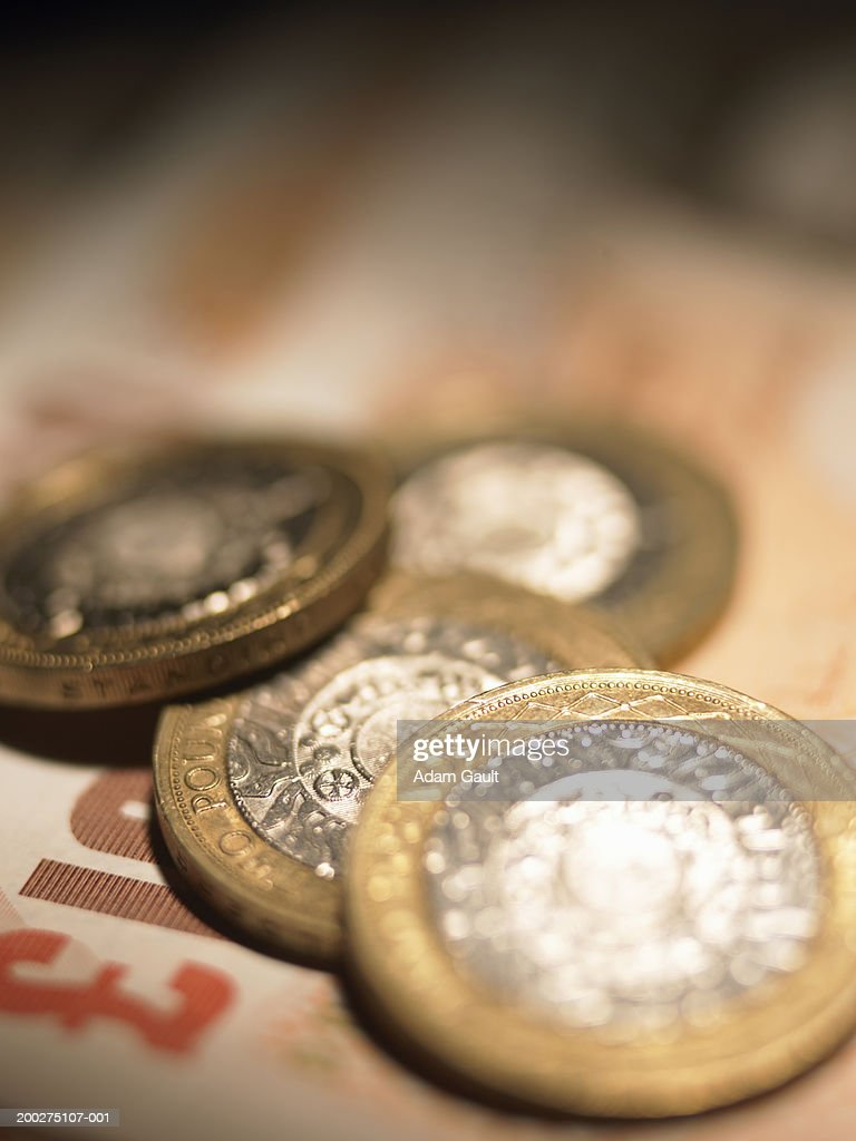 British Currency: Two pound coins on ten pound banknote, close-up