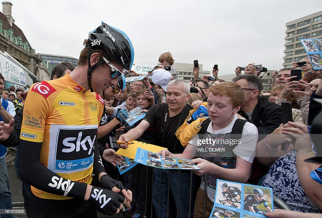 British cyclist Bradley Wiggins signs his autograph to fans before the start of the final stage of Tour of Britain in London on September 22, 2013. Bradley Wiggins won his home Tour of Britain as compatriot Mark Cavendish of Omega Pharma QuickStep cycling team took his third stage victory of this year's race.