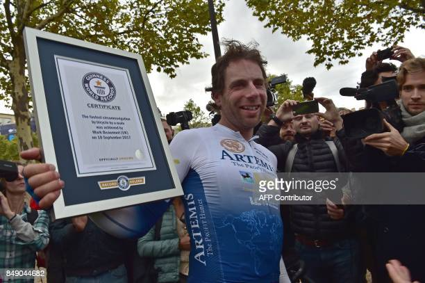 British cyclist Mark Beaumont holds a Guinness World Records certificate in Paris on September 18 2017 after he completed his journey around the...