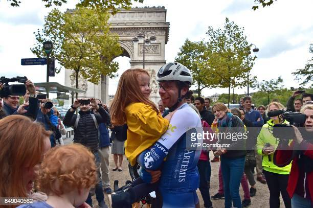 British cyclist Mark Beaumont holds his daughter after arriving at the Arc de Triomphe in Paris on September 18 2017 to complete his tour around the...