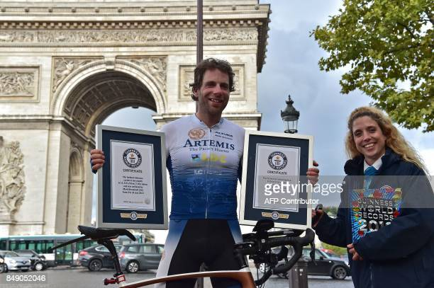 British cyclist Mark Beaumont poses for pictures with Guinness World Records certificates after arriving at the Arc de Triomphe in Paris on September...