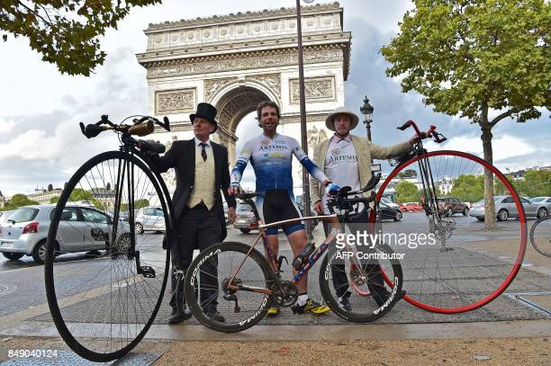 TOPSHOT British cyclist Mark Beaumont poses next to men with pennyfarthings after arriving in Paris on September 18 to complete his journey after he...