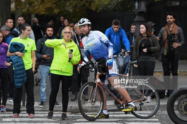 British cyclist Mark Beaumont speaks with a member of his team after arriving at the Arc de Triomphe in Paris on September 18 2017 to complete his...