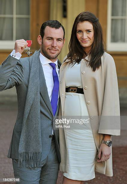 British cyclist Mark Cavendish stands with his partner Peta Todd as he proudly holds his MBE after he received it from Queen Elizabeth II at...