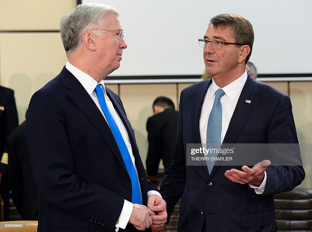 British Defence Minister Michael Fallon (L) and US Secretary of Defence Ashton Carter (R) talk together prior to a meeting of the North Atlantic Council (NAC) of Defence Ministers at the NATO headquarters in Brussels, February 10, 2016. NATO defence ministers convene a two-day meeting to discuss current defense issues and whether the Alliance should take a more direct role in dealing with its gravest migrant crisis since Worl War II. / AFP / THIERRY CHARLIER