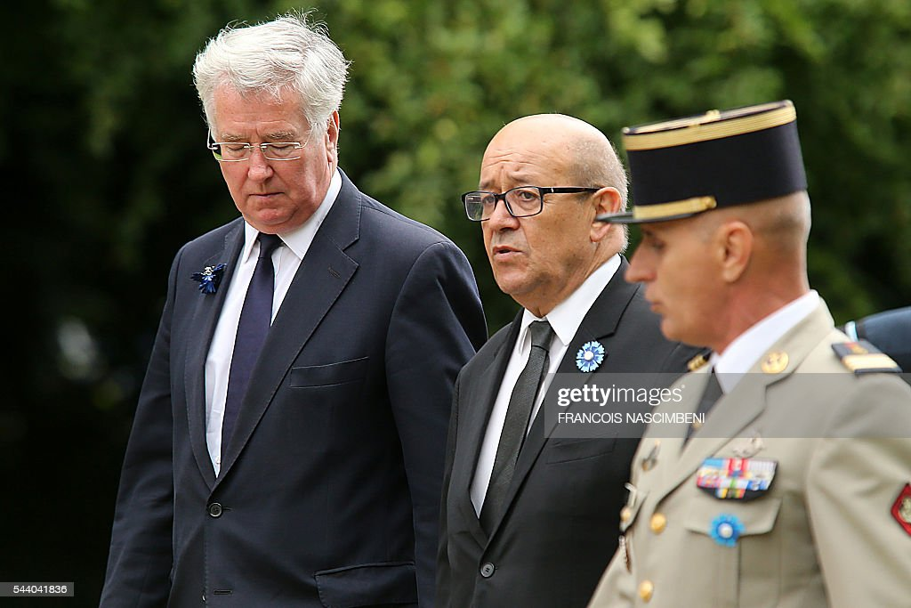 British Defence Secretary Michael Fallon (L) and French defence Minister Jean-Yves Le Drian (C) attend on July 1, 2016 a ceremony marking the 100th anniversary of the World War I battle at the River Somme at the Thiepval Memorial, northern France. Under grey skies, unlike the clear sunny day that saw the biggest slaughter in British military history a century ago, the commemoration kicked off at the deep Lochnagar crater, created by the blast of mines placed under German positions two minutes before the attack began at 7:30 am on July 1, 1916. / AFP / FRANCOIS