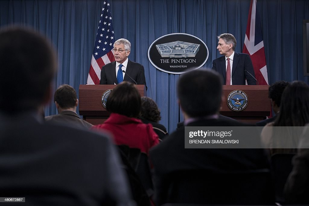 British Defense Secretary Philip Hammond (R) listens while US Secretary of Defense Chuck Hagel speaks during a press conference at the Pentagon on March 26, 2014 in Washington, DC. Hagel and Hammond held the briefing after a bilateral meeting earlier at the Pentagon where they spoke about the Ukraine and other issues. AFP PHOTO/Brendan SMIALOWSKI