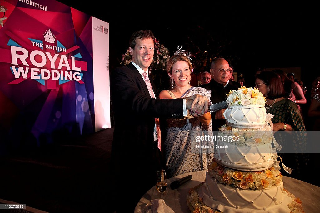British Deputy High Commissioner to India Nigel Casey (L) cuts a wedding cake with his wife Clare Casey at a function in the High Commissioners residence to celebrate the royal wedding on April 29, 2011 in Delhi, India. The wedding of Britain's Prince William and Kate Middleton took place at Westminster Abbey in London.
