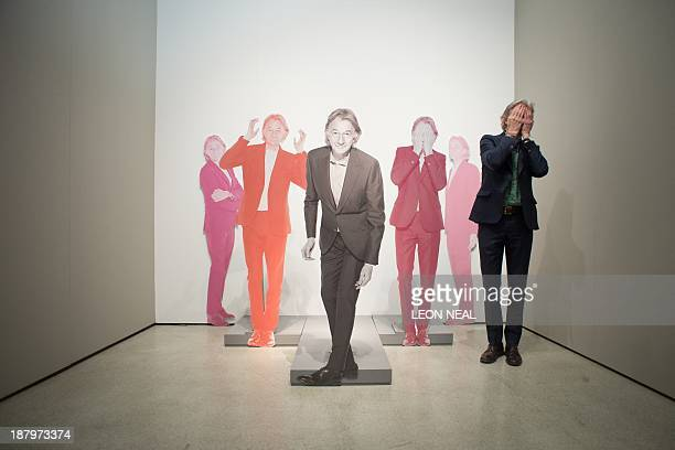 British designer Paul Smith poses with cardboard cutouts of himself at the opening of the 'Hello My Name is Paul Smith' exhibition at Design Museum...