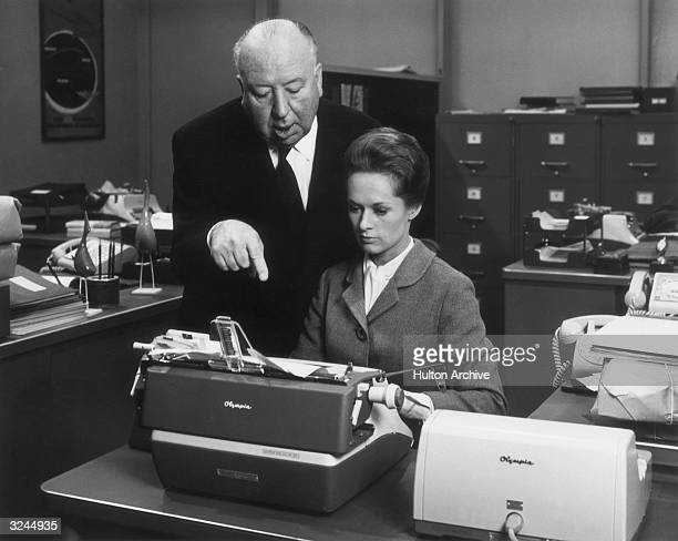 British director Alfred Hitchcock directs American actor Tippi Hedren while she sits in front of a typewriter on the set of his film 'Marnie'