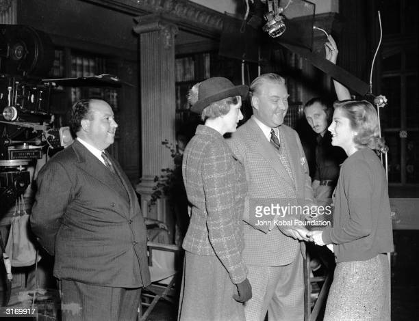 British director Alfred Hitchcock watching actors Gladys Cooper Nigel Bruce and Joan Fontaine on the set of his latest thriller 'Rebecca'