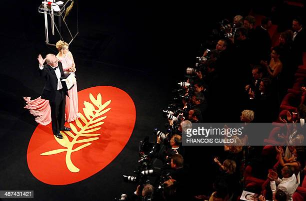 British director Ken Loach celebrates on stage next to French actress Emmanuelle Beart after winning the Palme d'Or during the closing ceremony of...