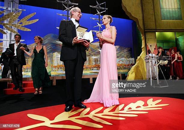 British director Ken Loach poses on stage next to French actress Emmanuelle Beart after winning the Palme d'Or during the closing ceremony of the...