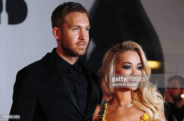British DJ Calvin Harris and British singersongwriter Rita Ora pose on the red carpet arriving at the BRIT Awards 2014 in London on February 19 2014...