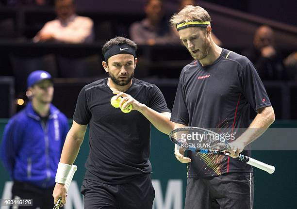 British Dominic Inglot with his doubles partner Romanian Florin Mergea gestures before to play against British Jamie Murray and Australian John Peers...