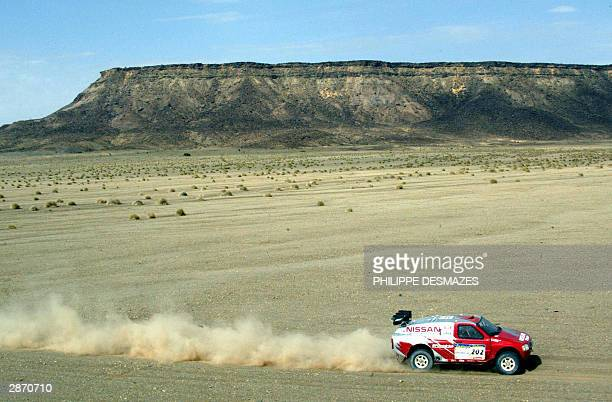British driver Colin McRae drives on Nissan 15th of January 2004 during the 14th stage between Ayoun El Atrouz and Tidjika in Mauritania during the...