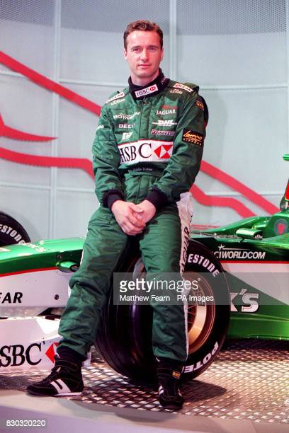 British driver Eddie Irvine sits on the wheel of the new Jaguar R003 Formula 1 racing car which was unveiled in Central London The car will compete...