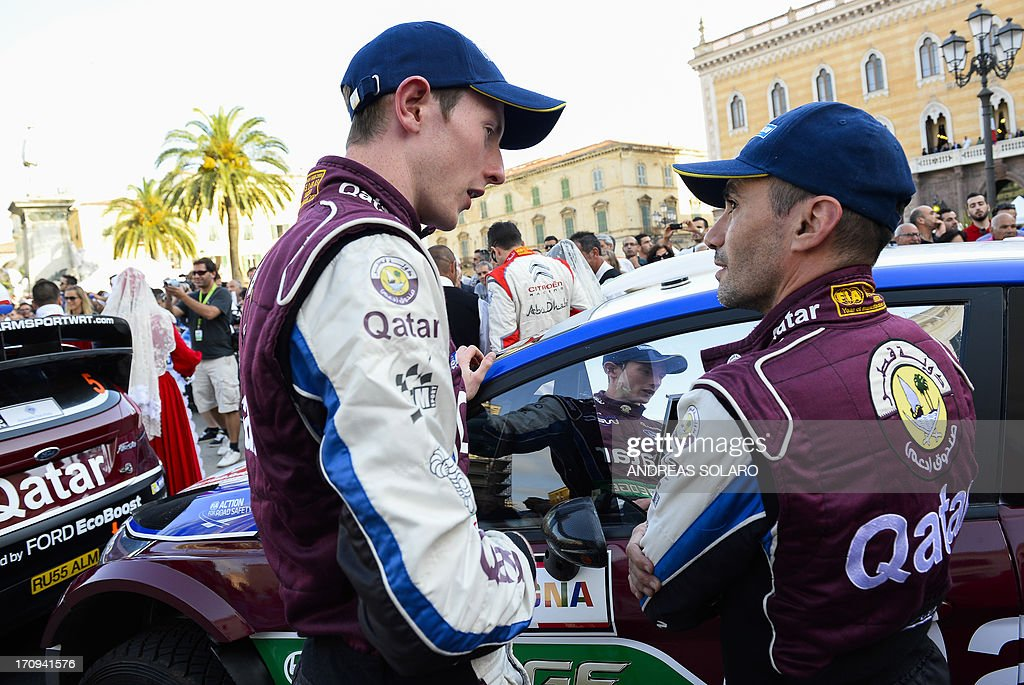 British driver Elfyn Evans (L) and co-driver Italy's Giovanni Bernacchini stand in front of their Ford Fiesta RS WRC during the opening ceremony of the FIA World Rally Championship of Italy in Sassari, on the Italian island of Sardinia on June 20, 2013. AFP PHOTO / ANDREAS SOLARO
