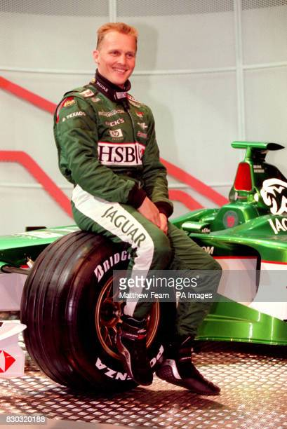 British driver Johnny Herbert sits on the wheel of the new Jaguar R003 Formula 1 racing car which was unveiled in Central London The car will compete...