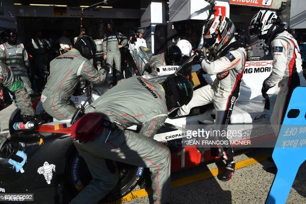 British driver Nick Tandy leaves the Porsche 919 Hybrid N°1 after competing as teammate German driver Andre Lotterer prepares to get in during the...