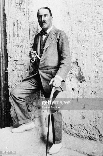 British Egyptologist Howard Carter stands with one foot up on a step at the entrance to an Egyptian archaeological site Egypt 1923
