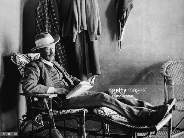 British Egyptology patron George Herbert Fifth Earl of Carnarvon reclines on a wooden easy chair and reads a book Egypt 1923