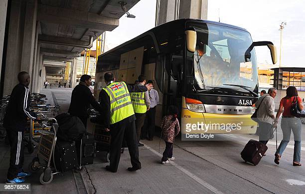 British embassy oficial helps people get onto the first passenger bus leaving Barajas airport carrying stranded British citizens on April 20 2010 in...