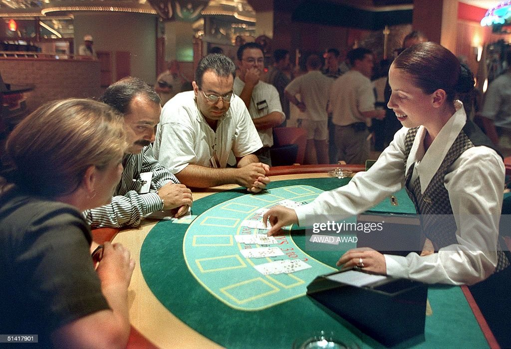 British employee deals a hand of black jack during a press tour of the first Palestinian casino in the West Bank town of Jericho 14 September one day...