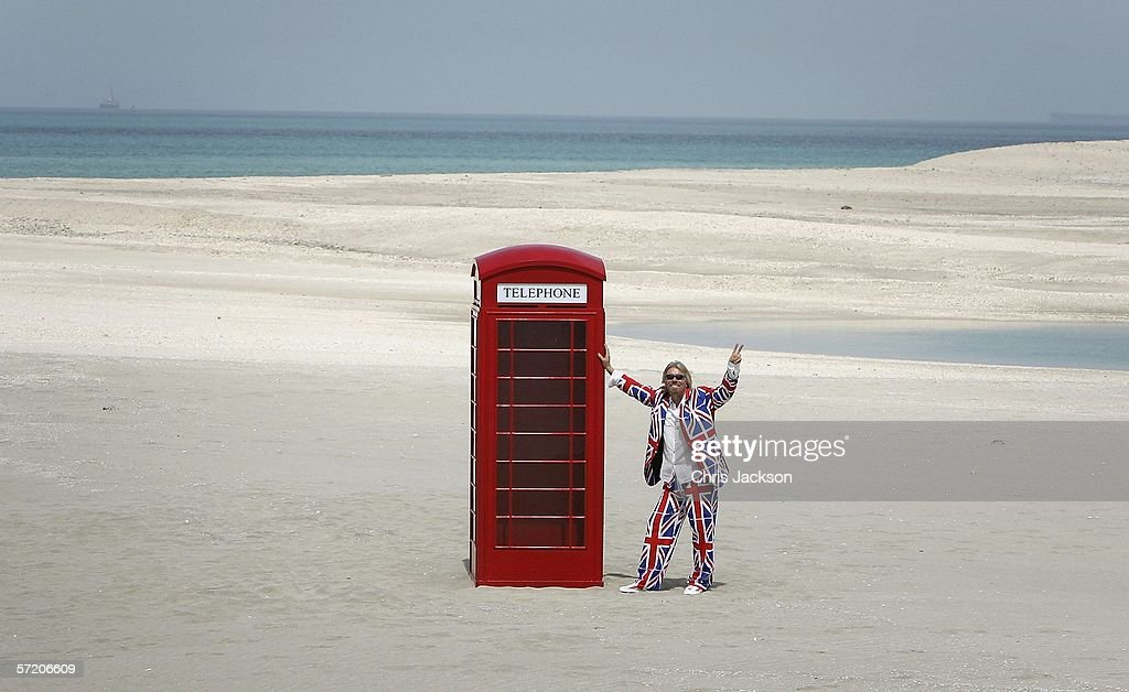 British Entrepreneur and businessman Sir Richard Branson poses next to a phone box during a photocall on a stretch of sand on the man-made island known as 'United Kingdom' in the new development, The World on March 29, 2006 in Dubai, United Arab Emirates. The World consists of over 300 man made islands strategically positioned to form the shape of the world map, lying 4km off the coast of Dubai.