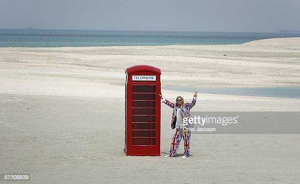 British Entrepreneur and businessman Sir Richard Branson poses next to a phone box during a photocall on a stretch of sand on the manmade island...