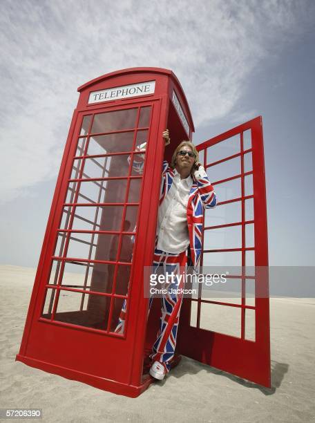 British Entrepreneur and businessman Sir Richard Branson poses on his phone in a phone box during a photocall on a stretch of sand on the manmade...