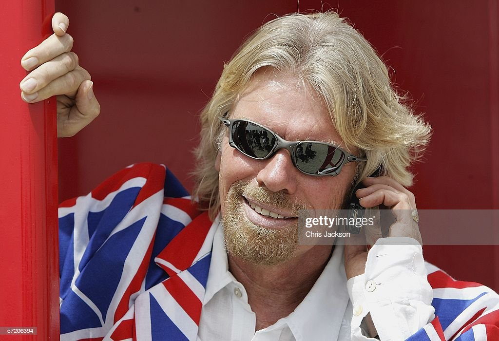 British Entrepreneur and businessman Sir Richard Branson poses on his phone in a phone box during a photocall on a stretch of sand on the man-made island known as 'United Kingdom' in the new development, The World on March 29, 2006 in Dubai, United Arab Emirates. The World consists of over 300 man made islands strategically positioned to form the shape of the world map, lying 4km off the coast of Dubai.
