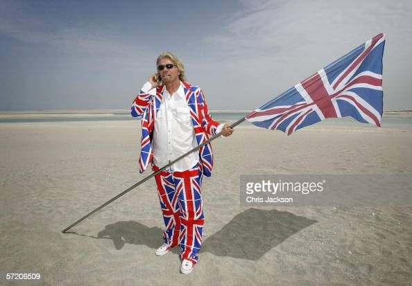 British Entrepreneur and businessman Sir Richard Branson poses with a Union Jack during a photocall on a stretch of sand on the manmade island known...