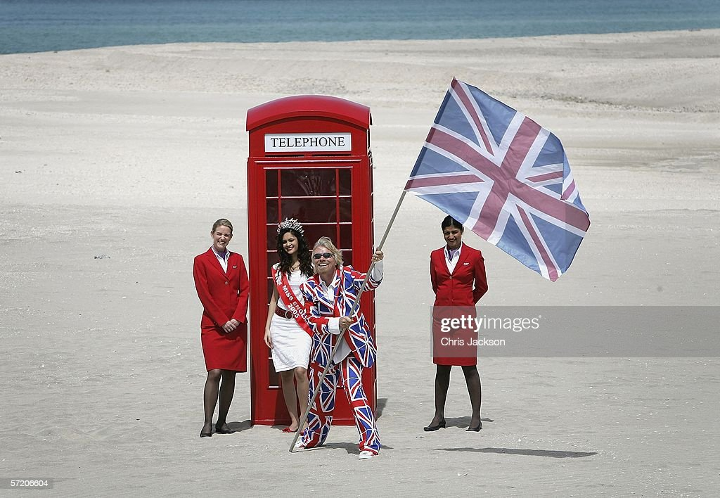 British Entrepreneur and businessman Sir Richard Branson poses with Miss England Hammasa Kohistani and Virgin girls next to a phone box during a photocall on a stretch of sand on the man-made island known as 'United Kingdom' in the new development, The World on March 29, 2006 in Dubai, United Arab Emirates. The World consists of over 300 man made islands strategically positioned to form the shape of the world map, lying 4km off the coast of Dubai.